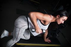 Młoda dziewczyna z plciową dętą postacią w gym dumbbell dźwignięciu, Zdjęcia Stock