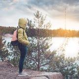 Młoda dziewczyna z plecakiem cieszy się widok jezioro zdjęcia stock