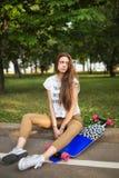 Młoda dziewczyna z smutnym twarzy obsiadaniem w parku z longboard Outdoors, styl życia zdjęcia royalty free