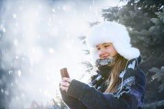 Młoda dziewczyna z telefonem komórkowym w zimie zdjęcie royalty free
