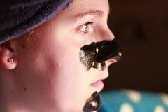 Młoda dziewczyna 20, 25 z węgiel drzewny maską na twarzy jako część piękno reżimu po brać prysznić Fotografia Stock