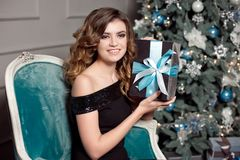 Młoda dziewczyna z wspaniałym falistym włosy, jaskrawy makeup, chwyty w jej rękach zawijający prezent, siedzi w barwiącym krześle obraz stock