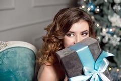 Młoda dziewczyna z wspaniałym falistym włosy, jaskrawy makeup, chwyty w jej rękach zawijający prezent, siedzi w barwiącym krześle zdjęcia stock