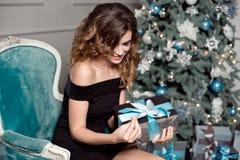 Młoda dziewczyna z wspaniałym falistym włosy, jaskrawy makeup, chwyty w jej rękach zawijający prezent, siedzi w barwiącym krześle fotografia stock