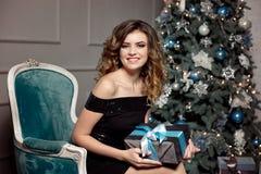 Młoda dziewczyna z wspaniałym falistym włosy, jaskrawy makeup, chwyty w jej rękach zawijający prezent, siedzi w barwiącym krześle obraz royalty free