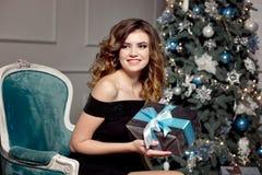 Młoda dziewczyna z wspaniałym falistym włosy, jaskrawy makeup, chwyty w jej rękach zawijający prezent, siedzi w barwiącym krześle zdjęcie royalty free