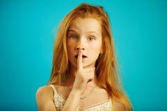 Młoda dziewczyna z zdumiewającym spojrzeniem stawia jej palec wskazującego wargi, wyraża znaczenie cisza lub sekretność, demonstr obraz royalty free