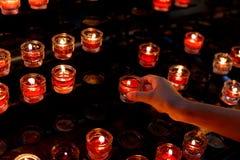 młoda dziewczyna zaświeca czerwoną świeczkę w kościół i wtedy mówi pra Zdjęcia Royalty Free