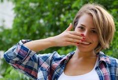 Młoda dziewczyna zakrywa jej uśmiech z jego ręką Fotografia Stock