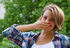 Młoda dziewczyna zakrywa jej uśmiech z jego ręką Zdjęcie Stock