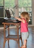 Młoda dziewczynka bawić się z laptopem Fotografia Stock