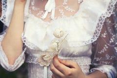 Młoda dziewicza dziewczyna trzyma kwiatu w białej koronkowej ślubnej sukni obraz stock