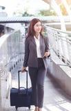 Młoda elegancka biznesowa kobieta z ręka bagażem i pastylka jesteśmy wa Obrazy Royalty Free