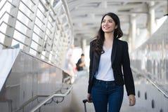 Młoda elegancka biznesowa kobieta z ręka bagażu odprowadzeniem wzdłuż sid Fotografia Stock