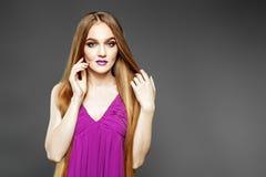 Młoda elegancka dziewczyna w purpury sukni Bardzo długie włosy przeciw jako tła popasu pojęcia dolarom szarość wiesza haczyka Obrazy Stock