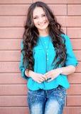 Młoda elegancka kobieta na ściana z cegieł backround Zdjęcie Royalty Free