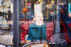Młoda elegancka kobieta pije kawę w kawiarni w Paryż, Francja Zdjęcie Stock