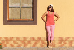 Młoda elegancka kobieta pozuje przeciw ścianie Fotografia Royalty Free