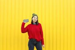 Młoda elegancka modniś dziewczyna ma zabawę i robi grymasom blisko jaskrawej żółtej miastowej ściany przy nocą z błyskiem Być ubr Zdjęcie Royalty Free