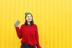 Młoda elegancka modniś dziewczyna ma zabawę i robi grymasom blisko jaskrawej żółtej miastowej ściany przy nocą z błyskiem Być ubr Obraz Royalty Free