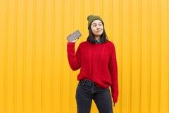 Młoda elegancka modniś dziewczyna ma zabawę i robi grymasom blisko jaskrawej żółtej miastowej ściany przy nocą z błyskiem Być ubr Obraz Stock