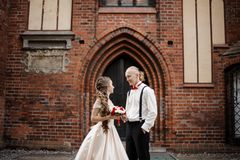 Młoda elegancka pary małżeńskiej pozycja i ono uśmiecha się w tle stary budynku łuk obrazy royalty free