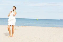 Młoda elegancka piękna kobieta opowiada na telefonie na plaży Fotografia Royalty Free