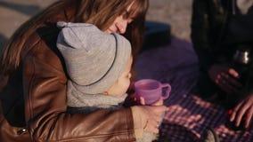 Młoda elegancka rodzina w casualwear obsiadaniu na szkockiej kracie nadbrzeżnym i mieć gorących napoje przy pinkinem Matka daje f zbiory wideo