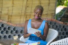 Młoda eleganckiego i eleganckiego czarnego afrykanina Amerykańska biznesowa kobieta pracuje przy modnym sklep z kawą używać cyfro Obrazy Royalty Free