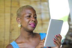 Młoda eleganckiego i eleganckiego czarnego afrykanina Amerykańska biznesowa kobieta pracuje przy modnym sklep z kawą używać cyfro Obraz Royalty Free