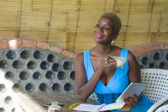 Młoda eleganckiego i eleganckiego czarnego afrykanina Amerykańska biznesowa kobieta pracuje przy modnym sklep z kawą używać cyfro Zdjęcia Royalty Free