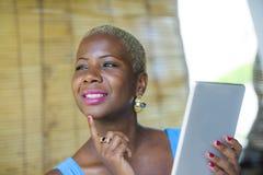 Młoda eleganckiego i eleganckiego czarnego afrykanina Amerykańska biznesowa kobieta pracuje przy modnym sklep z kawą używać cyfro Zdjęcia Stock