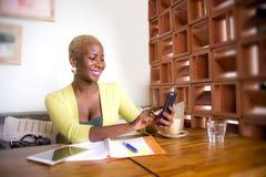 Młoda eleganckiego i pięknego czarnego afrykanina Amerykańska biznesowa kobieta pracuje online z telefonu komórkowego ono uśmiech Obraz Stock