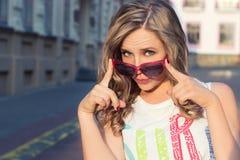 Młoda energiczna, szczęśliwa dziewczyna w czerwonych okularach przeciwsłonecznych w mieście na słonecznym dniu, zdjęcie royalty free