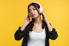 Młoda etniczna dziewczyna z ponytails fryzurą, utrzymania oba ręki na hełmofonach, słucha ulubioną piosenkę, odizolowywaj zdjęcia stock