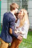 Młoda europejska atrakcyjna para jest stojąca i ściskająca blisko do zieleni ogrodzenia pod słońcem Piękna kobieta przewiduje cał Zdjęcie Stock
