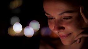 Młoda europejska kobieta siedzi outside przy nocą i spojrzenia zestrzelają zbiory