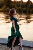 Młoda europejska kobieta stoi blisko jeziornej, pięknej europejskiej kobiety w naturze, ładna młoda kobieta w zielonej sukni obraz stock