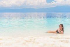 Młoda europejska kobieta w bikini z dobrym nastroju i marnieć spojrzeniem kłama w pięknym tropikalnym spokojnym morzu pod chmurną Obrazy Royalty Free