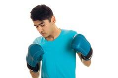 Młoda facet pozycja w bokserskich rękawiczkach i patrzeć w dół odizolowywający na białym tle Obrazy Royalty Free