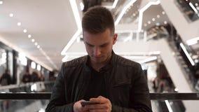 Młoda facet pozycja w zakupy centrum handlowym, używać smartphone zdjęcie wideo