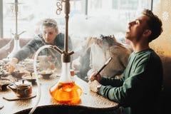 Młoda firma ludzie dymi nargile i komunikuje w orientalnej restauraci L obrazy stock