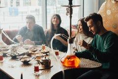 Młoda firma ma zabawę i je w barze dymić nargile, komunikuje w orientalnej restauraci obrazy stock