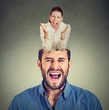 Młoda gniewna kobieta krzyczy inside głowę sfrustowany facet Fotografia Royalty Free