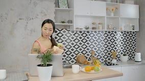 Młoda gospodyni domowa jest przyglądającym laptopu ekranem, chodzi wokoło domowej kuchni zbiory