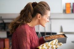 Młoda gospodyni domowa wącha wypiekowego naczynie z chlebem zdjęcia stock