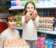 Młoda gospodyni domowa z małą dziewczynką wybiera wybierający jajko Zdjęcie Royalty Free