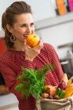Młoda gospodyni domowa z zakupami od miejscowego rynku łasowania jabłka Obrazy Stock