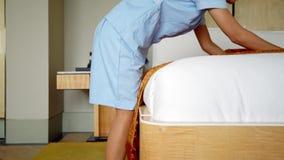 Młoda gosposi ułożenia koc na łóżku zbiory