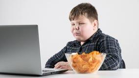 Młoda gruba chłopiec je układy scalonych i dopatrywanie kreskówki na laptopu 50 fps i zbiory